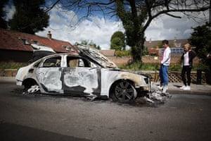 London Riots: Youths look at the remains of a burnt out car in Enfield