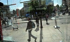 London Riots: A man walks past a damaged shop window on Brixton High Street