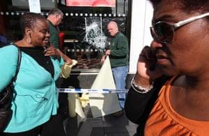 London Riots: Pedestrians walk past workers fixing a broken glass window at a McDonalds