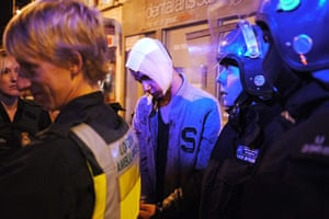 London riots day 3: An injured man is led to an ambulance handcuffs, Clapham Junction