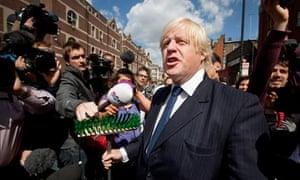 Boris Johnson addresses the crowd holding a broom in Clapham
