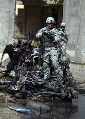 10 best: A US soldier inspects a bombed car in central Baghdad