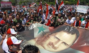 Syrians carry a flag bearing a picture of President Bashar Assad