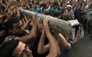 Egypt Riots: Protesters use a light pole to knock down a concrete wall in Cairo