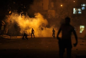 Egypt Riots: Protesters throw stones as tear gas rises at the Israeli embassy in Cairo