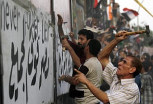 Egypt Riots: Protesters hammer a concrete wall in front of the Israeli embassy in Cairo