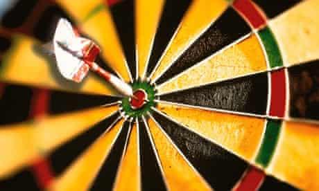 dart hitting dart board bulls eye
