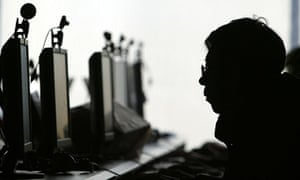 A computer user is silhouetted with a row of computer monitors at an internet cafe in China