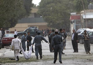 Kabul embassy attacks: Afghan policemen carry the body of a suicide attackerin Kabul