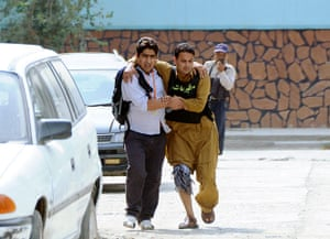 Kabul embassy attacks: A wounded man is helped away from the scene  of an attack  in Kabul
