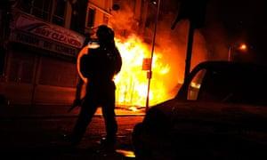 A riot policeman advances past a burning building in Croydon
