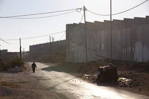 Al-Walaja: a woman walks past the wall