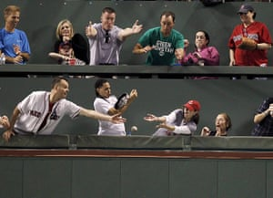 24 hours in pictures: Boston, US: Fans in the Green Monster seats reach for the ball