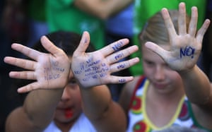 24 hours in pictures: Madrid, Spain: Children show their hands with slogans written on them