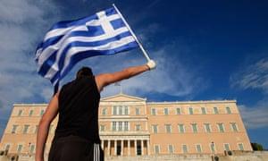 A protester raises Greek flag