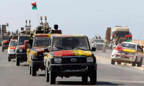 Anti-Gaddafi fighters ride on vehicles as they advance some 40 km (25 miles) west of Sirte