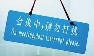 Sign with Chinese characters translated into English as 'On meeting, don't interrupt please'