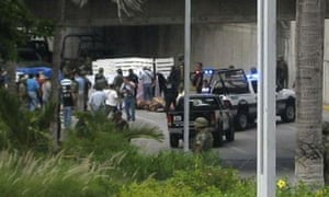 Police and forensic officers stand around some of the 35 bodies dumped on a motorway in Boca del Rio