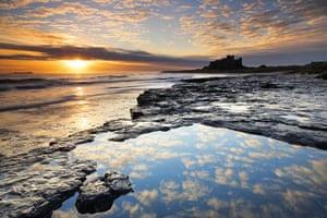 The Sea: The sun rises over the coast near Bamburgh Castle, Northumberland