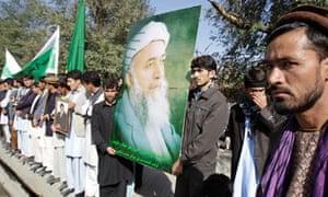 Mourners hold a poster of former Afghan president Burhanuddin Rabbani