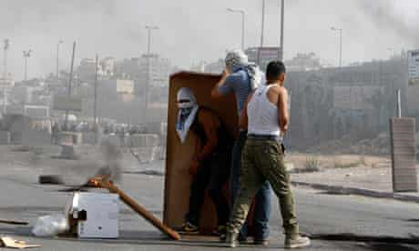 Palestinian protesters use furniture as a shield during clashes with Israeli security officers