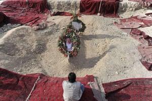 Rabbani funeral: A mourner prays at Rabbani's graveside