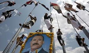 Yemeni supporters of President Ali Abdullah Saleh scale up flag poles to celebrate his return