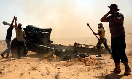 Libyan NTC fighters fire a heavy artillery piece near Sirte