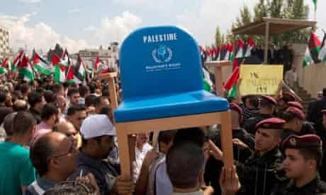 Palestinians in Ramallah carry a chair representing their seat at the UN