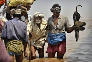 24 hours in pictures: Kasimpurchak, India: Villagers wade through flood waters