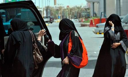 Saudi women get into the backseat of a car
