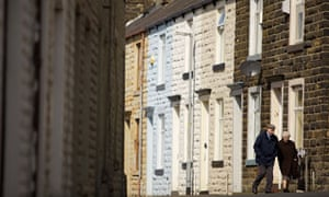 Pensioners walking pased a terraced house in Burnley, Lancashire.