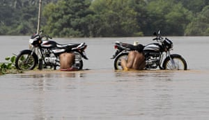 24 hours in pictures: Locals clean their motorbikes on a flooded road Patamundi, India