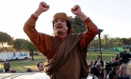 Libyan leader Muammar Gaddafi waving from a car in the compound of Bab Al Azizia in Tripoli