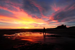 Hot Weather in the UK: A man walks his dog at sun rise near Bamburgh Castle in Northumberland