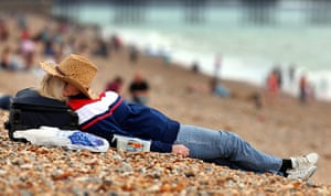 Hot Weather in the UK: A sunbather enjoys the beach in Brighton, East Sussex