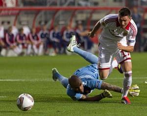 Europa League: Wisla Krakow's Andraz Kirm skips over FC Twente goalkeeper Nikolay Mihaylov