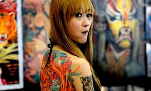 A woman displays her tattoo