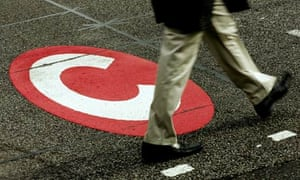 A man walks past a congestion charge sign on the road.