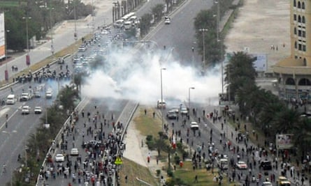 Tear gas explodes among protesters on a main road