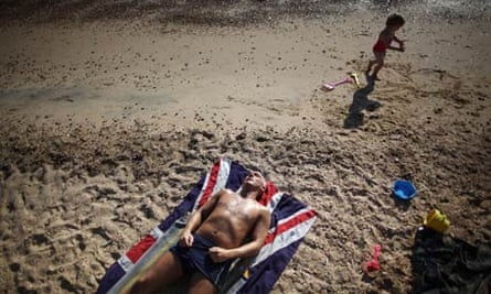 A man lies on the beach on a union flag towel