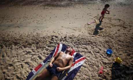A man lies on the beach on a union flag towel