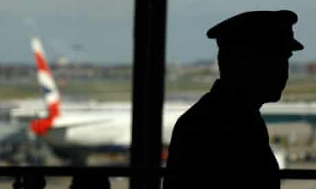A pilot waits in the departure lounge of BA's Terminal Five at Heathrow Airport