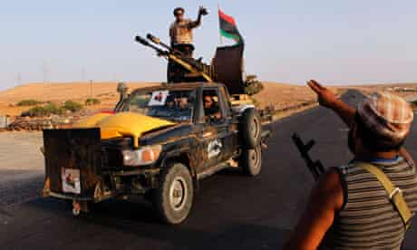 Anti-Gaddafi fighters pass by at the last checkpoint to enter the town of Bani Walid,