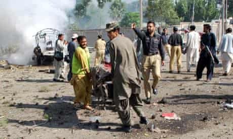 Pakistani security personnel carry injured blast victims