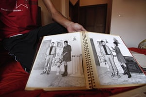 Gaddafi family photos: A Libyan rebel fighter shows photographs of Muammar Gaddafi with his wife
