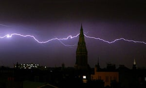 Lightning flashes behind church spire in London