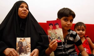 The mother and son of Baha Mousa hold pictures of him at their house in Basra
