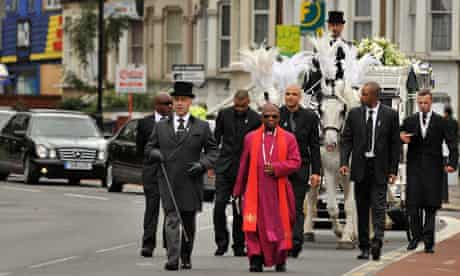 A horse-drawn funeral carriage carrying the coffin of Mark Duggan