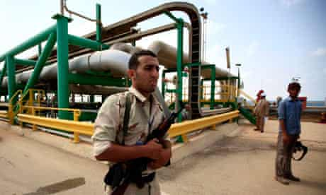 A Libyan fighter stands guard at the Mellitah oil and gas complex
